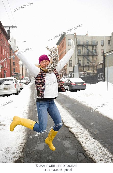 USA, New Jersey, Jersey City, woman jumping on street