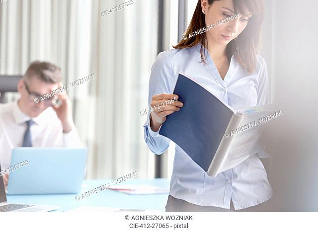 Focused businesswoman reading report in office