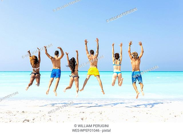 Group of friends at the beach, jumping for joy