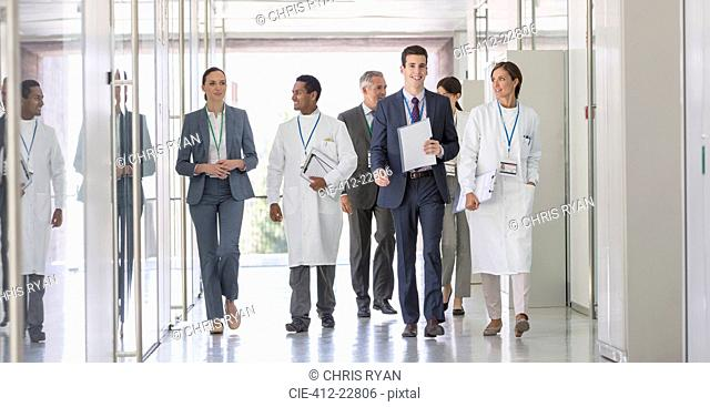 Scientists and business people walking in hallway
