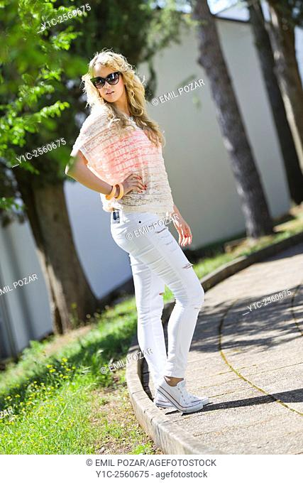 Posing young blonde woman in park hand on hip