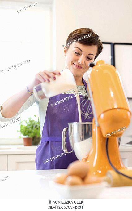 Smiling woman baking, using stand mixer in kitchen