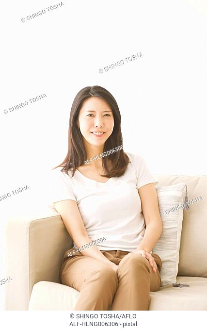 Young Japanese woman on the sofa in a white room