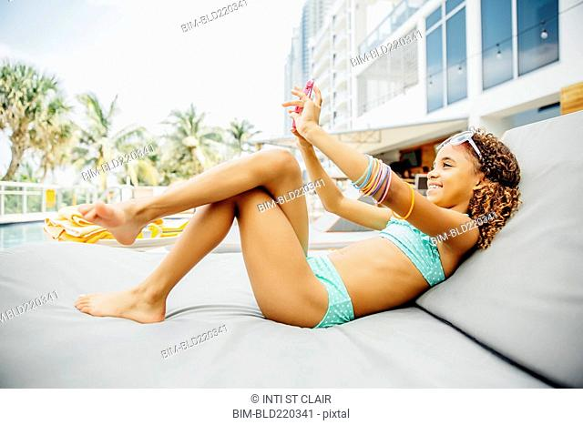 Mixed race girl taking selfie with cell phone on patio