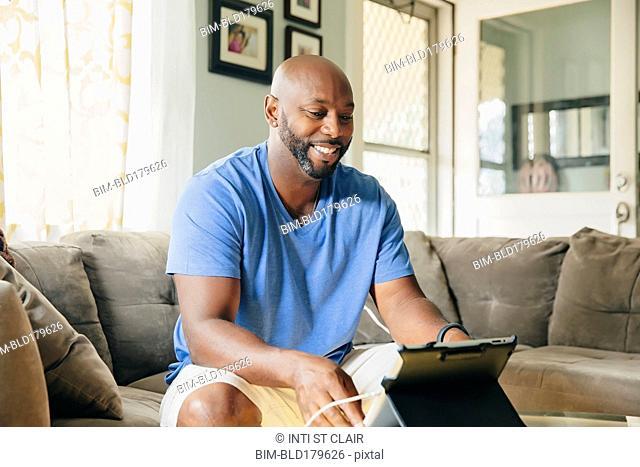 Black man using digital tablet in living room