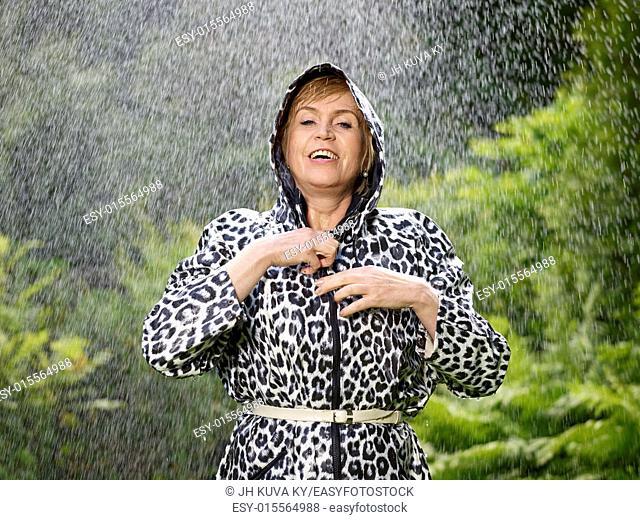 Mature woman wearing raincoat, rainy summer day, green nature on background