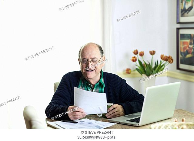 Senior man looking at documents on desk at home