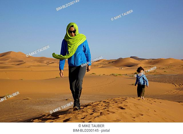Mother and son walking in desert