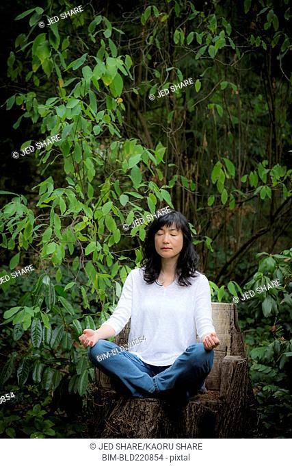 Japanese woman meditating in garden
