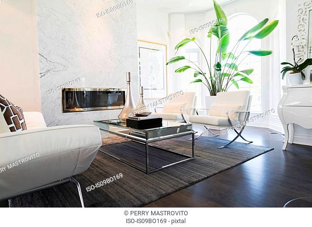 Living room with white leather and chrome sofa and matching armchairs facing coffee table inside luxury residential home