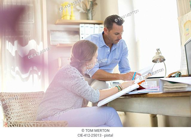 Father helping teenage daughter with her homework