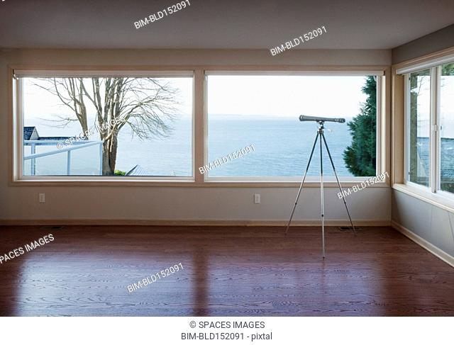 Telescope looking out living room window to ocean