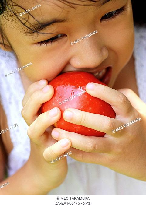 Close-up of a girl biting an apple