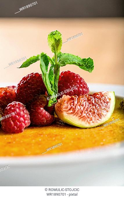 Crème brûlée with raspberries and mint, close-up