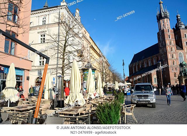 Restaurant terraces and partial view of Saint Mary's Church in the Rynek Glowny -Main Square-. Krakov, Poland, Europe
