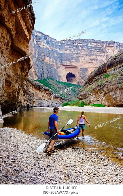 Couple carrying kayak into river, Big Bend National Park, Texas