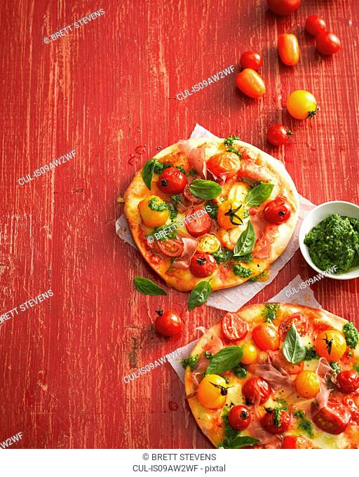 High angle view of tomato, basil and prosciutto pizzas