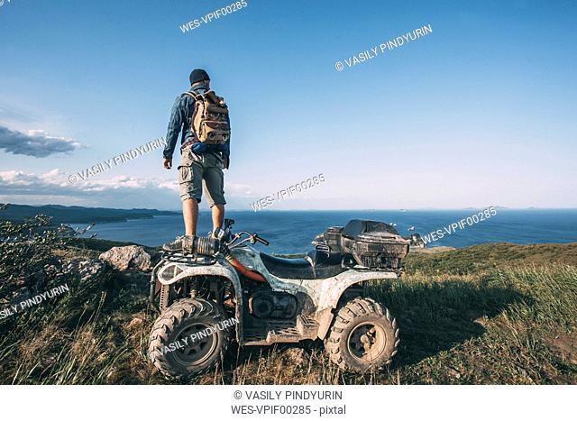 Russia, Far East, Khasanskiy, man with quadbike at the Japanese sea