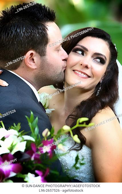 bride and groom at garden wedding embrace while groom kisses brides cheek