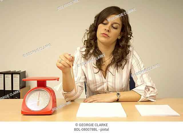 bored secretary sitting at desk holding pencil