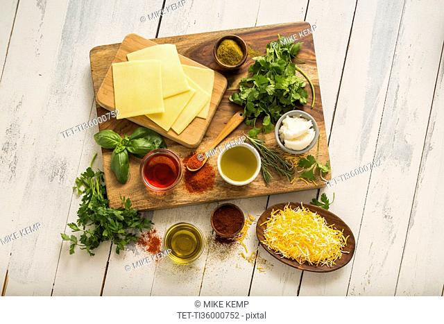Cheese, herbs and spices on cutting board