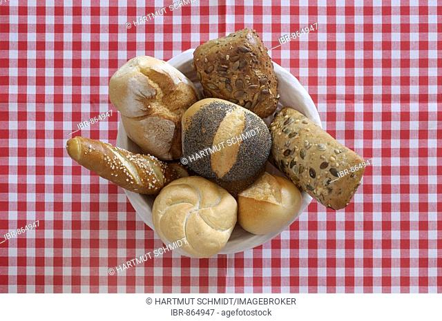 Bread, bread basket with various rolls on a red and white chequered table cloth