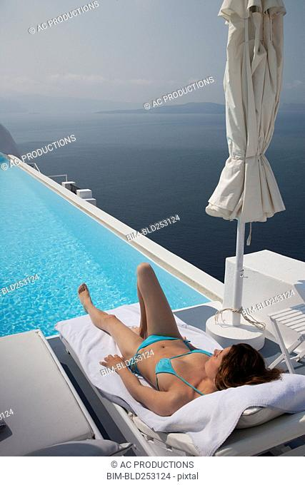 Caucasian woman laying on deck chair near swimming pool