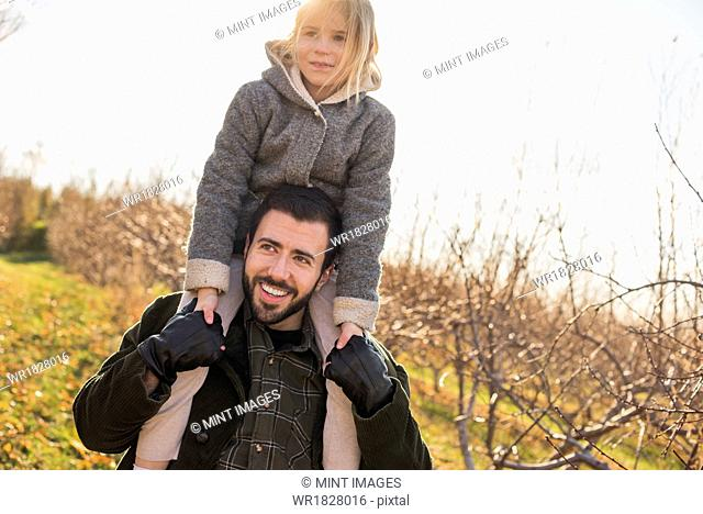 A man giving a child a ride on his shoulders