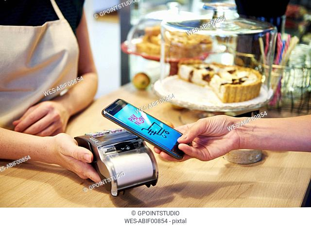 Customer paying cashless with smartphone in a cafe