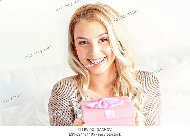 holidays, birthday, morning and people concept - happy young woman gift box or present at home