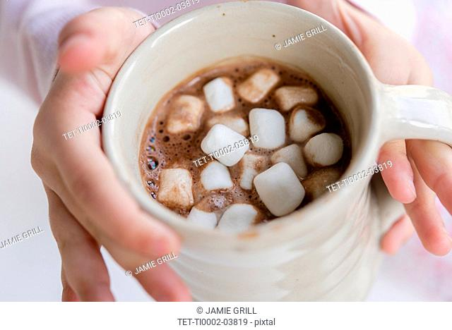 Hands of girl holding hot chocolate with marshmallows