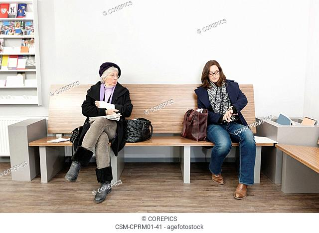Two women witing impatiently in the waiting room of a medical practice, with the doctor running late on his schedule