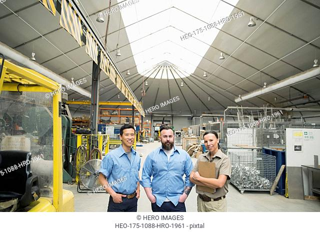Portrait of workers near forklift in manufacturing plant