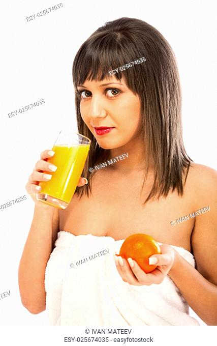 Young woman in towel drinking orange juice, looking at camera, isolated on white background