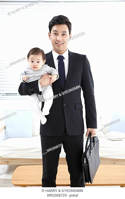 a business man holding a baby