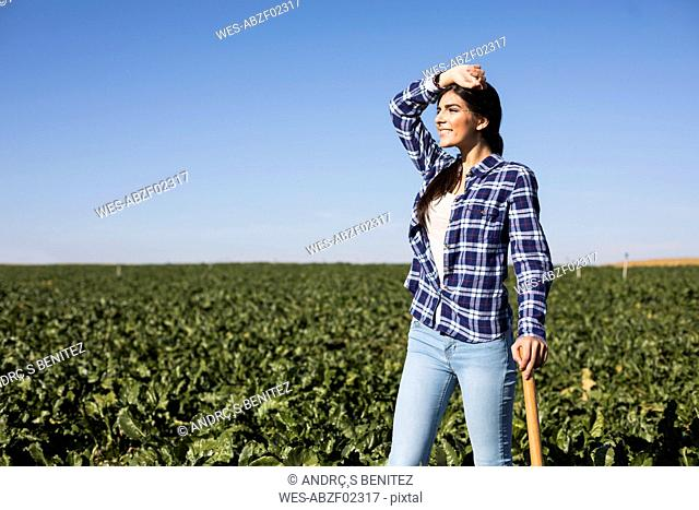 Young woman farmer with hoe on field