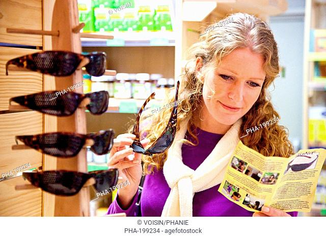 Woman reading brochure about grid glasses