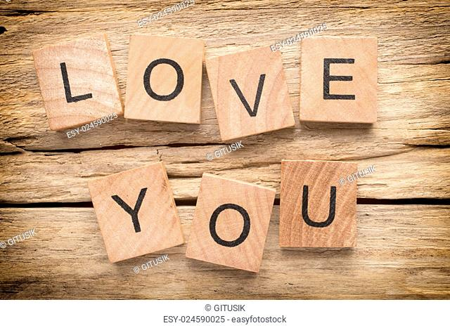 Wood heart on old wooden background - Stock Image. I love you, cast out of wood kubik