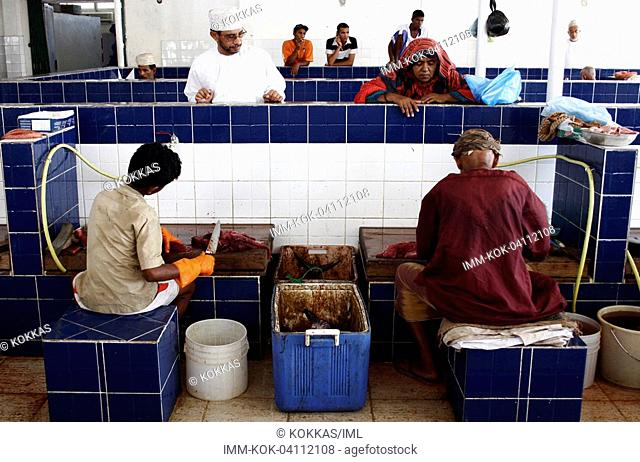 Mutrah, fish market, young men cleaning fishes , Muscat, Oman, Middle East