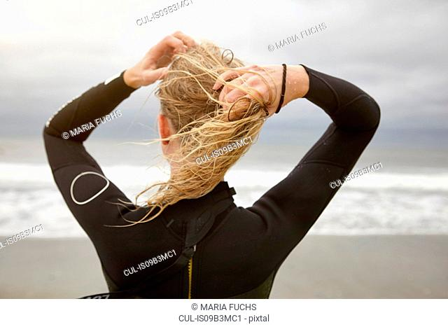 Rear view of female surfer tying wet blond hair on Rockaway Beach, New York, USA