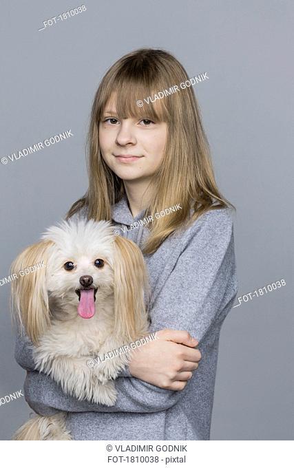 Portrait smiling tween girl holding dog