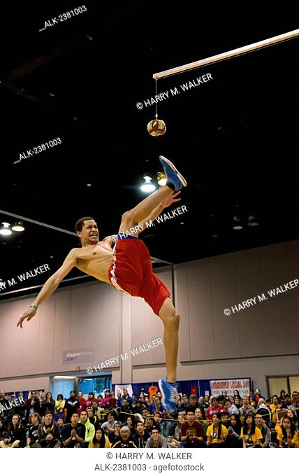 Athlete in mid air attempting to kick seal skin ball in Boy's One-Foot High Kick competition, 2013 Native Youth Olympics