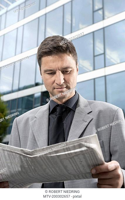 Businessman reading a financial newspaper outside office building, Bavaria, Germany