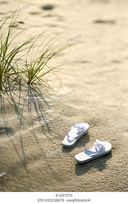 Two white sandals on sandy beach