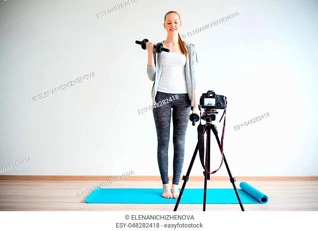 Female fitness blogger doing exercises at home