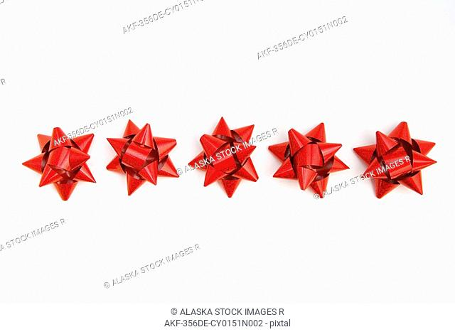 Five bright red Christmas gift bows in row on white background studio portrait