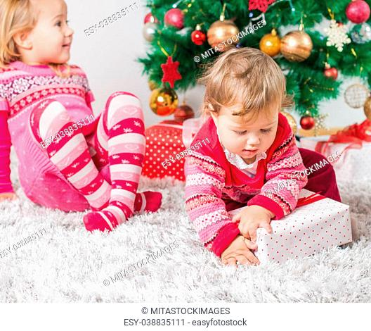Charming happy children open Christmas presents on the floor and tree with New Year decoration at home
