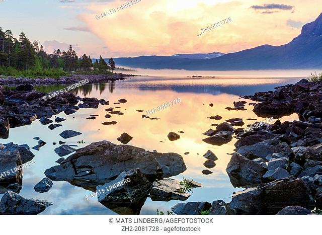 Dawn at stora sjöfallets national park with sun reflecting in the water and mountains in the background in Gällivare swedish lapland, Sweden