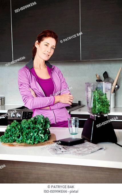 Mature woman making vegetable juice