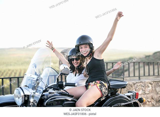 Portrait of two laughing women with their sidecar motorcycle